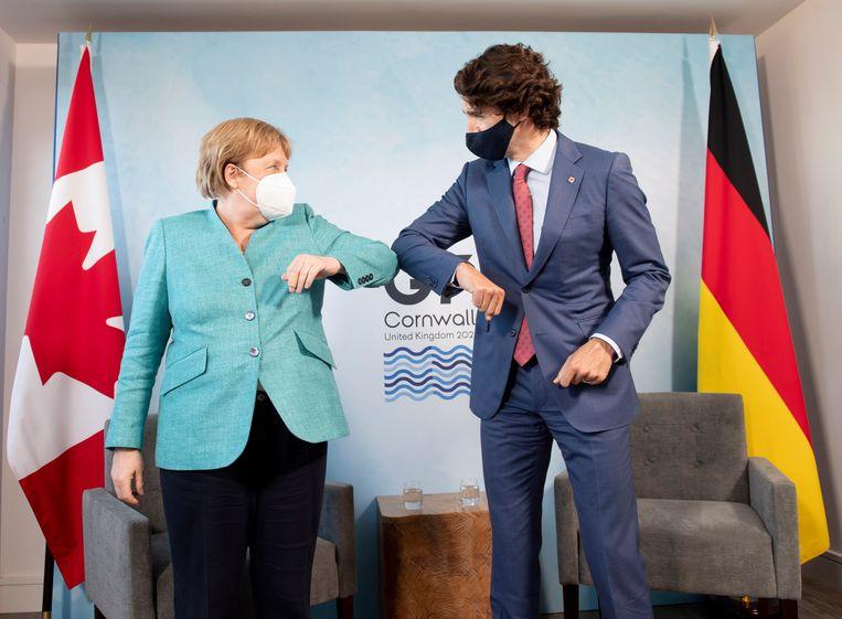 De Duitse Bondskanselier Angela Merkel en de Canadese premier Justin Trudeau begroeten elkaar op de G7-top in Cornwall. Beeld AP
