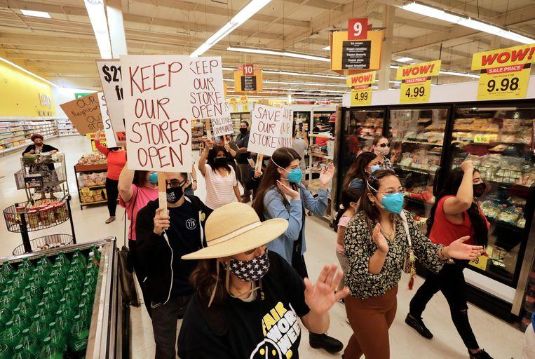 Protest tegen de sluiting van Krogersupermarkten in Los Angeles. Een verplicht extra 'heldenloon' voor het personeel zou de reden zijn.  Beeld Getty Images