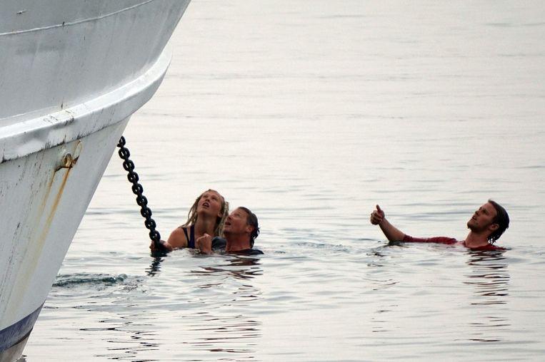 Activisten zijn in het water gesprongen en proberen de boot tegen te houden die de migranten naar Turkije terug zal brengen. Beeld afp