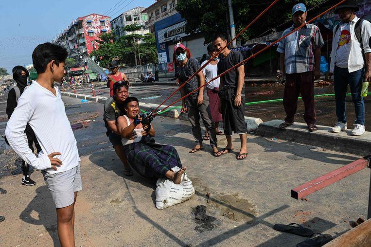 Bij gebrek aan echte wapens hebben demonstranten in Yangon een enorme katapult gefabriceerd. Beeld AFP