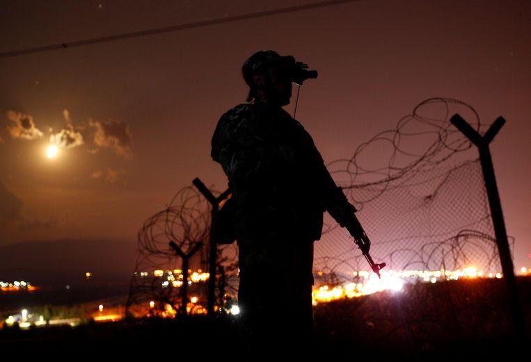 Een soldaat patrouilleert langs de grens tussen Macedonië en Griekenland.  Beeld REUTERS
