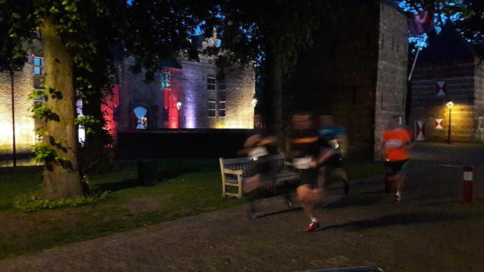 Deelnemers aan een eerdere editie van de NightRun passeren het Helmondse kasteel. Het pad achter de waterburcht wordt ditmaal verlicht.