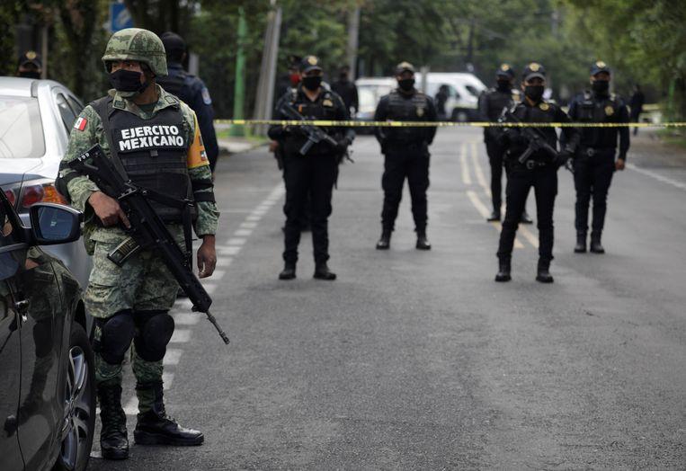 Een soldaat en politieagenten op de plaats in Mexico City waar een aanslag werd gepleegd op het hoofd van de veiligheidsdienst.