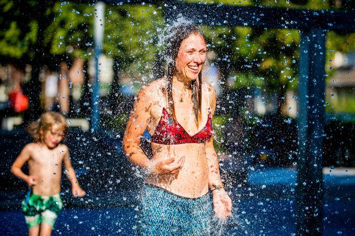 Een vrouw zoekt verkoeling in een fontein aan het Van Beuningenplein in Amsterdam op een bloedhete dag in juli tijdens de eerste hittegolf in drie jaar tijd.