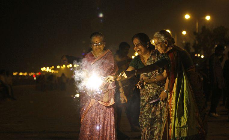 Vrouwen steken vuurwerk af tijdens het festival. Beeld null