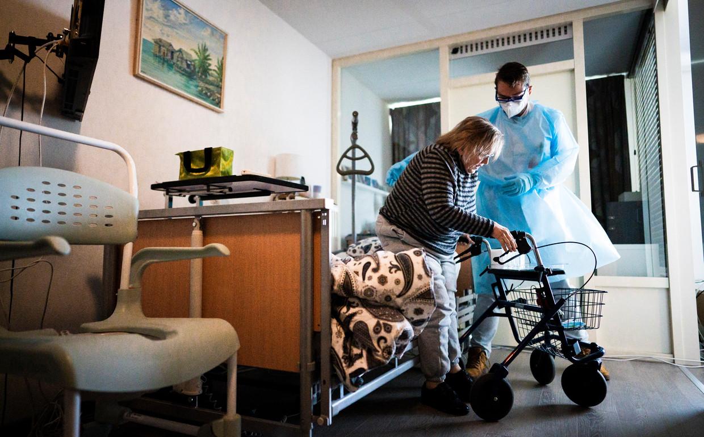 Verpleegkundige Arjo Verheijen helpt coronapatiënt mevrouw Van de Poll in haar woning in Rotterdam.  Beeld Freek van den Bergh / de Volkskrant