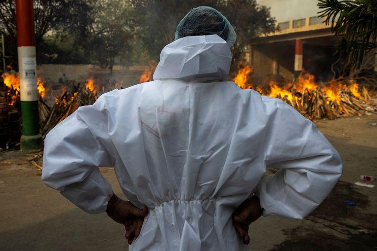 Abhishek Bhardwaj kijkt toe tijdens een massacrematie van coronaslachtoffers, onder wie ook zijn moeder. Beeld REUTERS