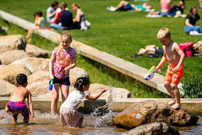 Kinderen spelen in het water in het Tilburgse Spoorpark. Na een koude periode met veel regen lokt de zon veel mensen naar buiten.