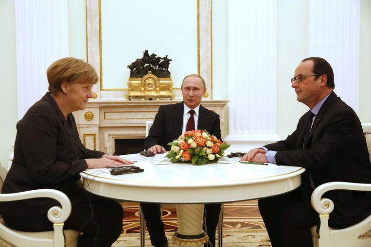 De Duitse bondskanselier Angela Merkel en de Franse president Francois Hollande tijdens hun ontmoeting met de Russische president Poetin, op vrijdagavond. Beeld AFP