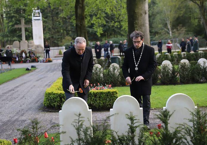 Locoburgemeester Peter de Rooij (rechts) legt een gerbera bij een graf op het Ereveld.