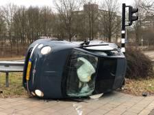 Auto op zijn kant door botsing in Eindhoven, bestuurder lichtgewond