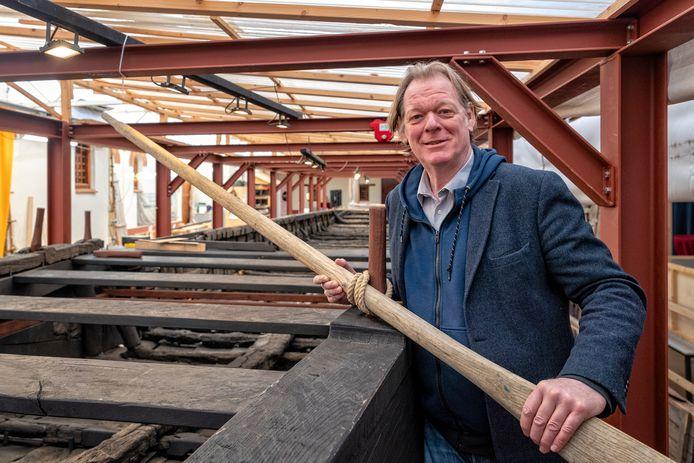 Archeoloog en projectleider Tom Hazenberg toont een gereconstrueerde boordplank met de pen waaraan de roeiriem wordt bevestigd.