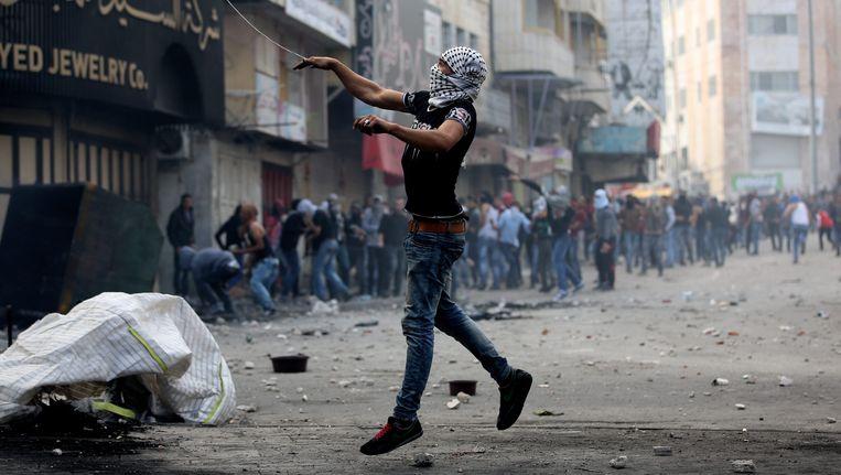 Een Palestijn gooit een steen tijdens de rellen vandaag bij de Gazastrook. Beeld EPA