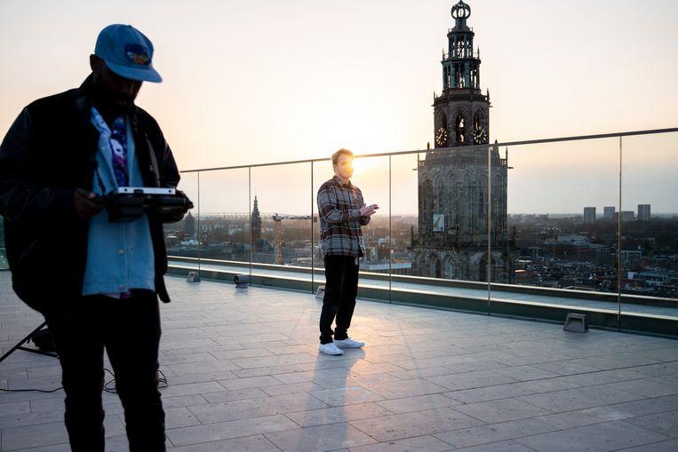 Filmopnamen in de laagstaande zon op het dak van het Forum.  Beeld David Vroom