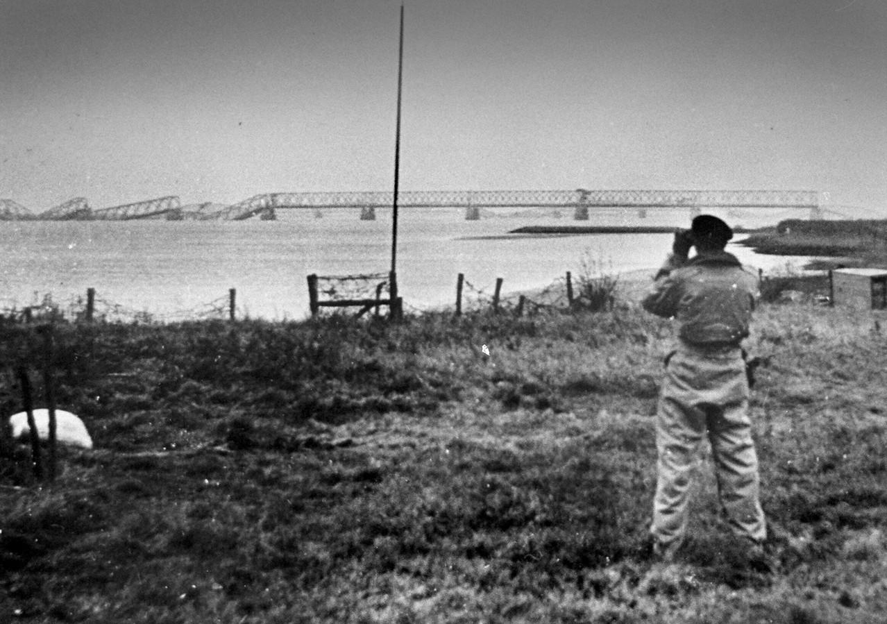 Een Poolse bevrijder kijkt in november 1944 vanaf Moerdijk naar de vernielde bruggen.
