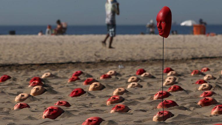 Het strand van Copacabana in Rio de Janeiro ligt vol met rode maskers om de onkunde van de Braziliaanse politici aan te klagen. In totaal liggen er 595 maskers in het zand, die alle nationale politici, inclusief president Temer, verbeelden. Beeld EPA