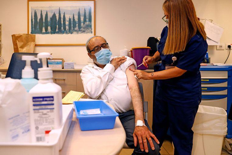 In een medisch centrum nabij Tel Aviv (Israël) krijgt een man voor de derde keer het Pfizer-vaccin toegediend. Beeld AFP