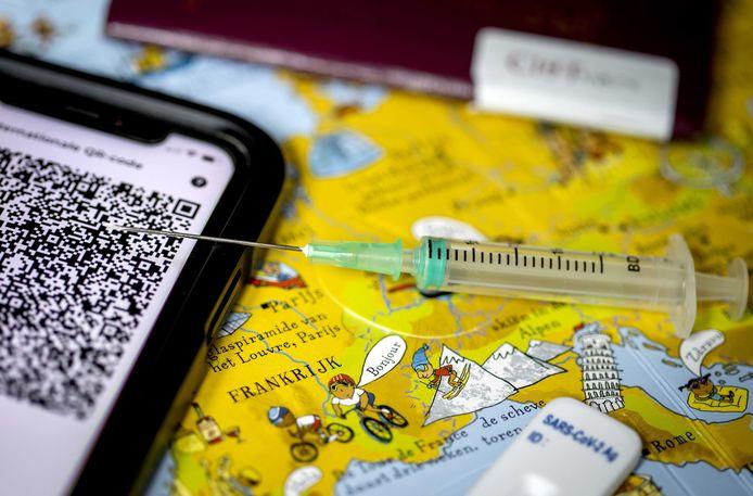 Een paspoort, vaccinatiebewijs, coronazelftest en CoronaCheck app met een internationale QR-code op een wereldkaart. Door het toenemende aantal coronabesmettingen komen de vakantieplannen van Nederlanders mogelijk in gevaar.
