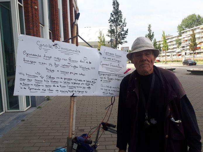 Een bewoner van de Zuidelijke Steijnkade staat bij het Huis van de Stad. Hij wil dat de gemeente de hoge bomen voor zijn woning weghaalt.