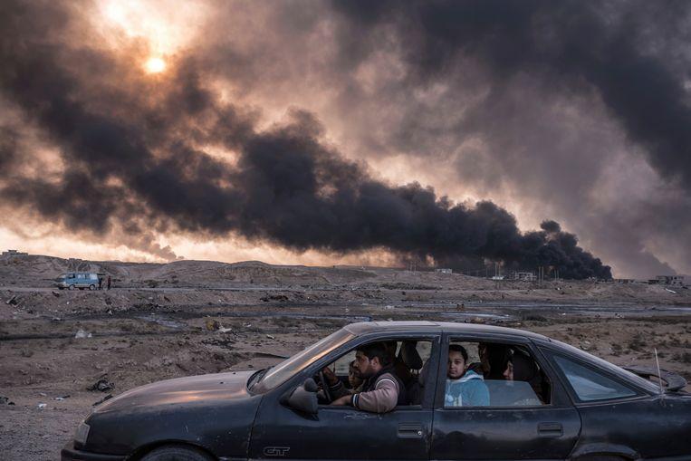 Irak, 2016. Een familie ontvlucht de gevechten in Mosul, terwijl in Qayyara oliebronnen branden die zijn aangestoken door IS.  Beeld AP