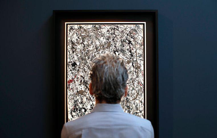 Een bezoeker aanschouwt 'No 19', een ander werk van Jackson Pollock, in het veilingshuis van Christie in New York. Beeld REUTERS