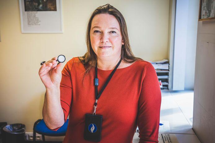 Evi Vandendriessche met het mobiele stalkingalarm: een eenvoudige,  witte knop die je aan het bandje van je bh kan bevestigen