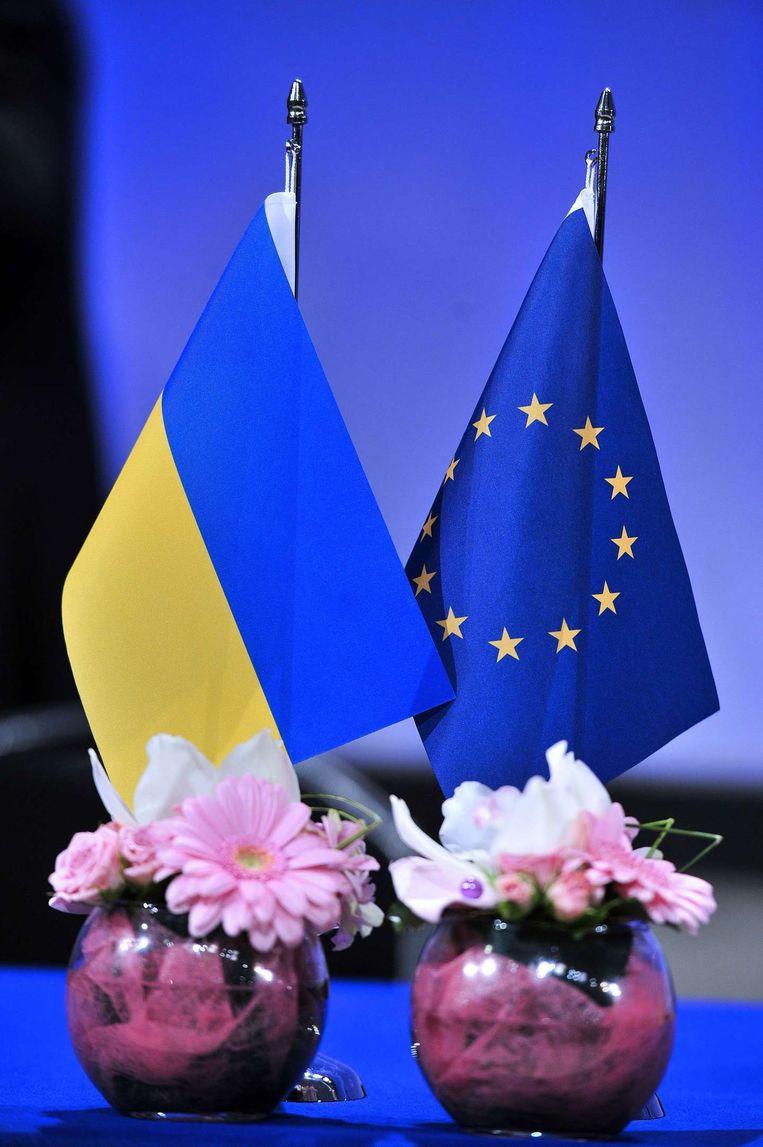 Een Oekraïense en Europese vlag bij de ondertekening van de overeenkomst