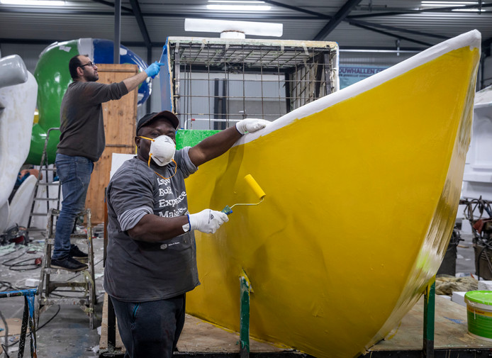 Asielzoekers Sheky Kargbo (met mondkap) en Omar Jabakji werken mee aan een carnavalswagen in Budel.