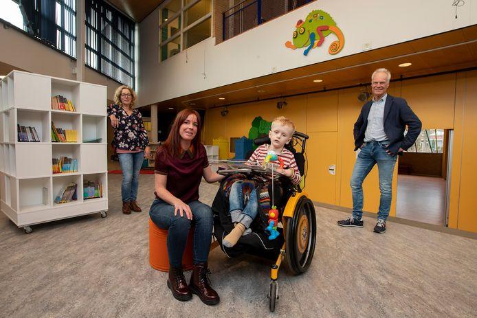 Anouk Valstar met Maas. Naast hen directeur Theo Molendijk en leerkracht Evelien van der Heijden.