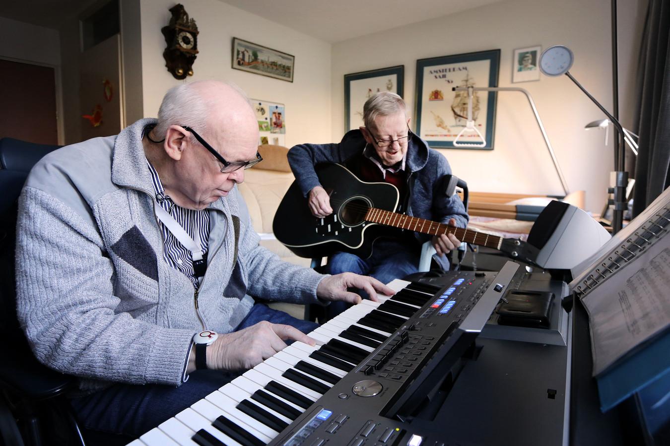 Frans Brandenburg (r) en Hans de Waart (l) repeteren voor het kerstconcert dat ze morgen geven voor hun medebewoners.