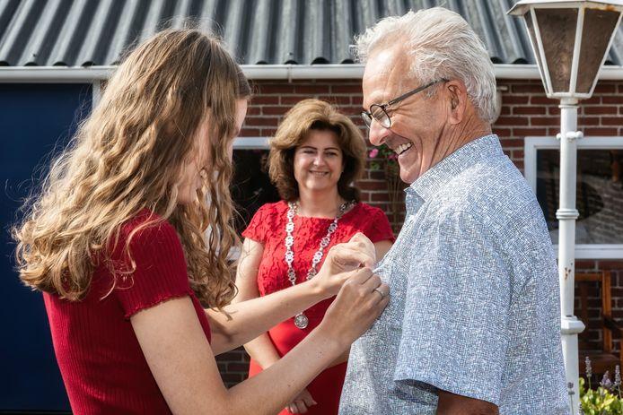 Piet Prinsen krijgt zijn lintje opgespeld door zijn kleindochter Fabienne Prinsen, terwijl burgemeester Marian Witte van gepaste afstand toekijkt.