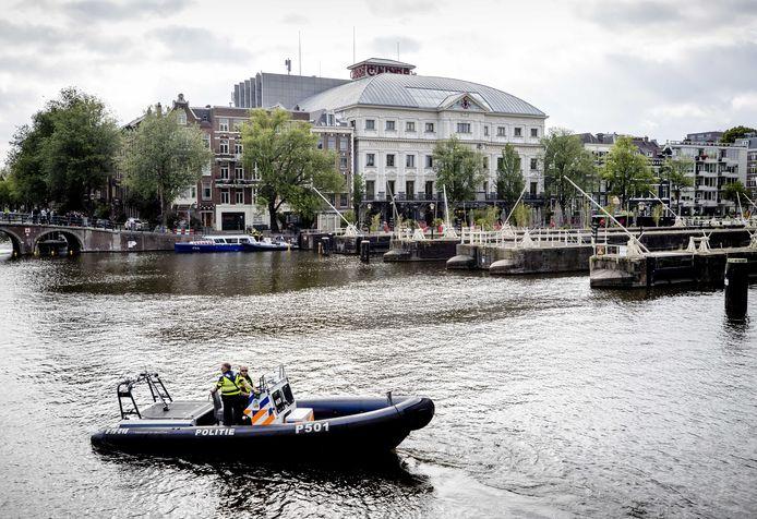 Een politieboot in de Amstel voor Theater Carré.