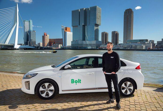 Lars Speekenbrink, country manager Nederland bij Bolt, bij een herkenbare Bolt-taxi. Chauffeurs die voor het logo kiezen, krijgen daarvoor betaald.