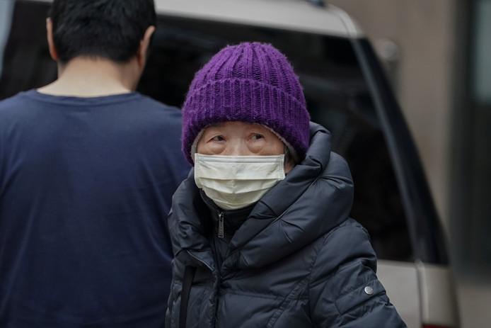 Een Chinese vrouw draag een mondkapje in China Town in New York.