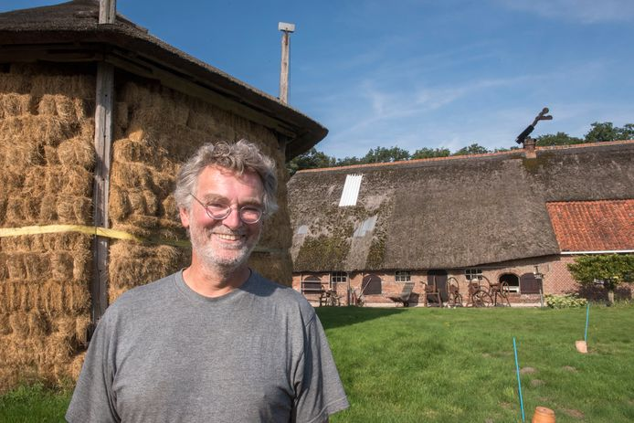 Eigenaar Ton Hoogstraat bij zijn boerderij Groot Hell in Putten, het. Rijksmonument dat nu wordt gerestaureerd. De scheefgezakte hooiberg werd hersteld, net als het rieten dak van de boerderij waar nu golfplaten de regen tegenhouden. het schuine ding op het dak is de 'gek'.