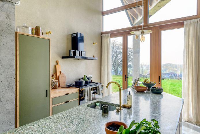 De combinatie van twee goedkope materialen – larikshout en groene mdf – levert een verrassend resultaat op in de keuken.