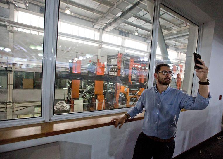 Een medewerker van de drukkerij van El National in Caracas maakt nog even een selfie terwijl de laatsten kranten gedrukt worden. Beeld AP