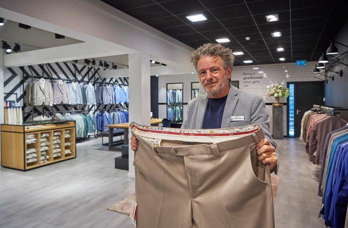 Verkoper Harry van den Berg toont een grote maat bij Van Tilburg Mode in Nistelrode.