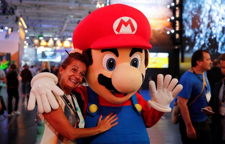 Een fan poseert met Mario op de Gamescom in Keulen. Beeld REUTERS