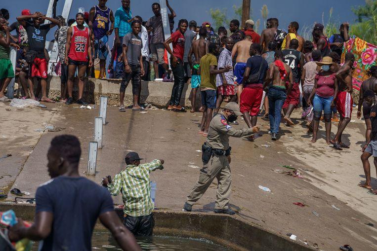 Texaanse politieagent probeert gestrande Haïtiaanse migranten bij de grensstad Del Rio in beweging te krijgen. Beeld AFP