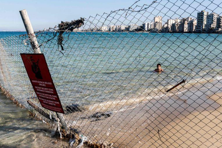 Een kind zwemt achter een hek in de betwiste badplaats Varosha op Cyprus. Beeld AFP