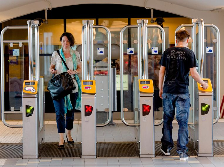 Reizigers lopen door het toegangspoortje op het station in Woerden. Beeld anp