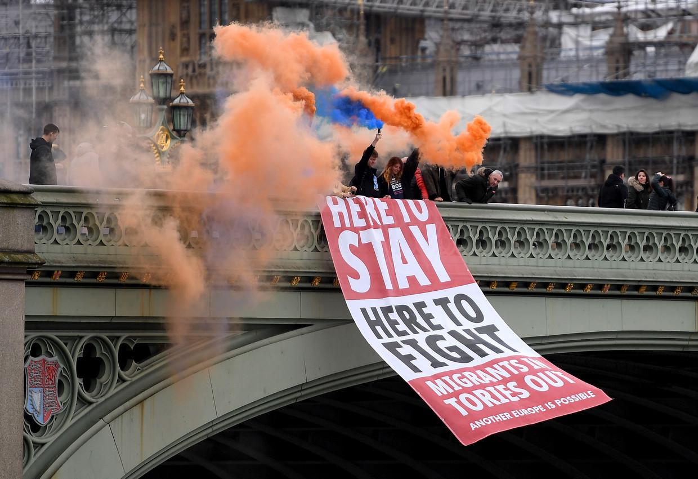 Strijdlustig tot het einde: anti-Brexit-betogers rollen luttele uren voor het Britse vertrek uit de EU bij het parlementsgebouw in Londen een banier uit met onderaan de leus 'Migranten erin, Tory's eruit'.  Beeld Foto Andy Rain / EPA