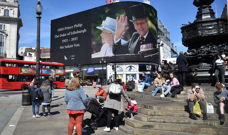 Beelden van de Britse prins Philip worden op een gigantisch scherm getoond in Piccadilly Circus, Londen. Beeld AP