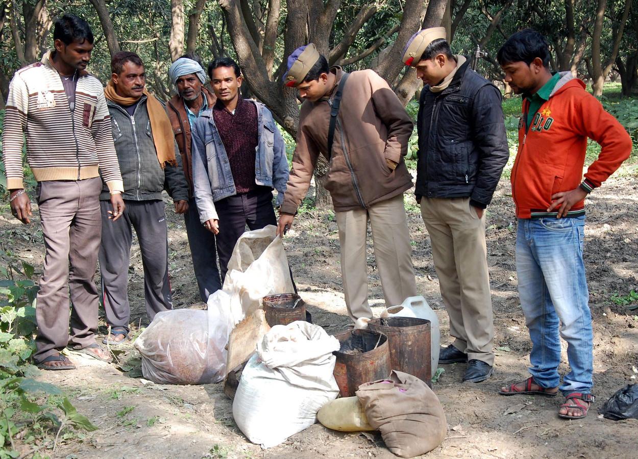 Mannen bij de restanten van een illegale stokerij (archiefbeeld 2014).