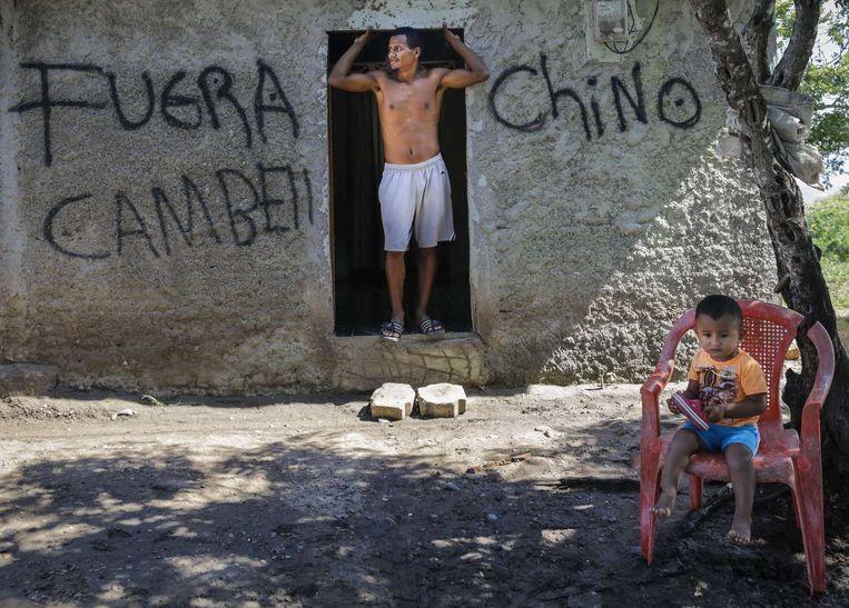 Een man staat in de deuropening van zijn huis. Op de muur is te lezen: 'Chinezen ga weg'. Beeld anp