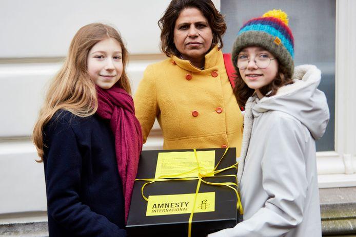 Gulnar Tabassum biedt met scholieren handtekeningen aan bij de Pakistaanse ambassade.