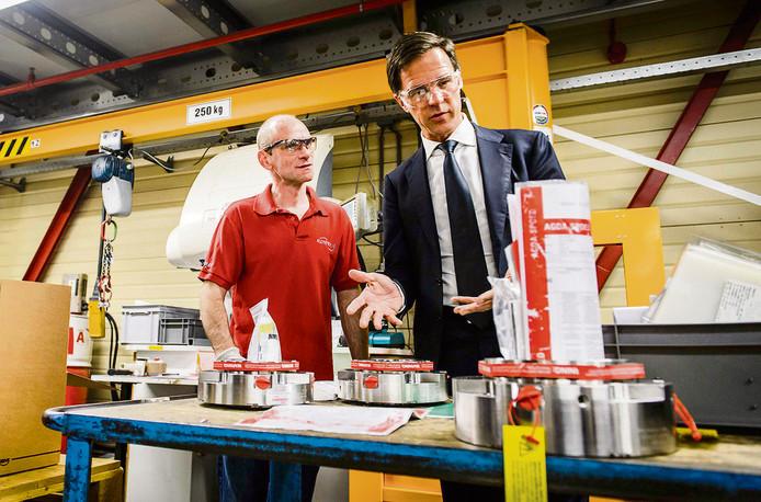 Premier Mark Rutte praat met een werknemer van een vestiging van Flowserve tijdens een werkbezoek aan de regio West-Brabant.
