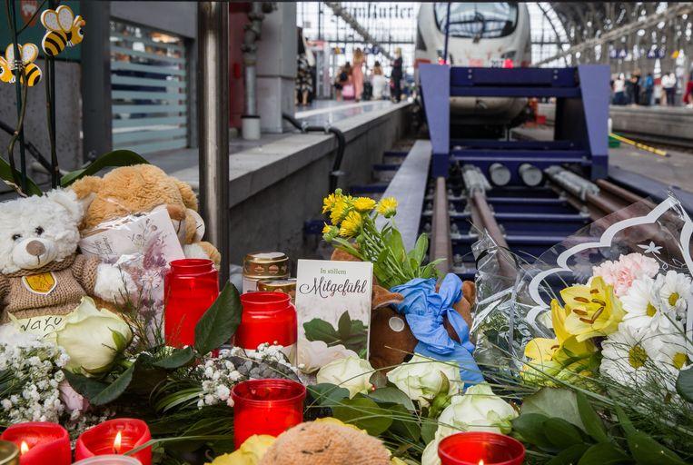 Mensen leggen bloemen en knuffelberen aan spoor 7 waar het jongetje het leven liet. Beeld Frank Rumpenhorst/dpa