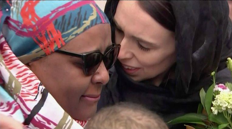 De Nieuw-Zeelandse premier Jacinda Ardern troost een vrouw bij een wake in Wellington voor de slachtoffers van de aanslag in Christchurch. Beeld AP